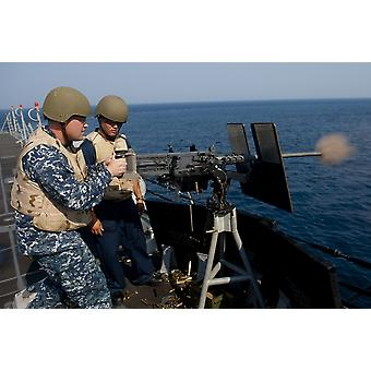 Atlantic Ocean June 21 2012 - Sonar Technician fires a 50 cal machine gun as Gunners Mate instructs during a training exercise aboard the guided-missile destroyer USS Jason Dunham Poster Print