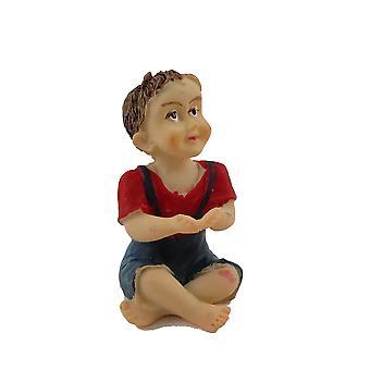 Nukketalo istuu pieni poika punainen yläosa miniatyyri ihmiset nasta moderni hahmo