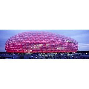Jalkapallostadion palaa ylös hämärän Allianz Arena Münchenissä Saksassa Juliste Tulosta