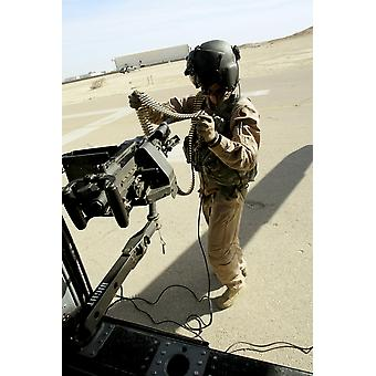 March 7 2006 - Soldier carries 762 mm rounds to a M240G medium machine gun aboard a UH-60 Blackhawk helicopter at Al Asad Iraq Poster Print