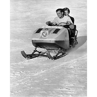 Mid adult couple riding a snowmobile downhill Poster Print