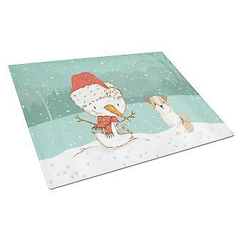 Ruskea ja valkoinen terrieri lumi ukko joulua lasin leikkuu lauta suuri
