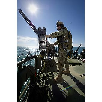 Gunner mans a M240 machine gun on a Riverine Command Boat Poster Print