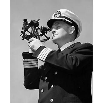 Low angle view of a ship captain looking through a sextant Poster Print