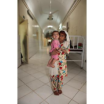 Afghan girl with baby in a hospital Helmand Province Afghanistan Poster Print by VWPicsStocktrek Images