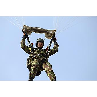 A member of the British Army Pathfinder Platoon prepares to land from a parachute jump Poster Print