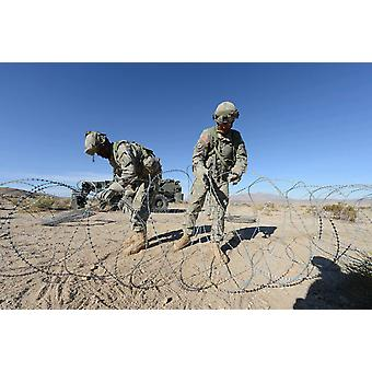 Soldiers uncoil concertina wire at Fort Irwin California Poster Print by Stocktrek Images