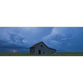 Lightning strikes over the prairies as it approaches an old abandoned farm house Val Marie Saskatchewan Canada PosterPrint