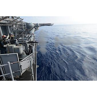 Sailors fire a 25mm machine gun aboard USS Bonhomme Richard Poster Print by Stocktrek Images