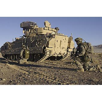 January 24 2007 - US Army Soldiers provide security with an M2 Bradley Fighting Vehicle outside a mock town during the National Training Center 0704 mission readiness exercise at Fort Irwin California