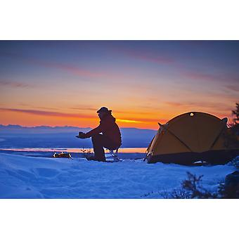 A backpacker warms his hands over a campfire at a campsite high in the Chugach Mountains overlooking Kinik Arm and Cook Inlet with Sleeping Lady in the background Southcentral Alaska PosterPrint