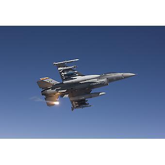 Un F-16 Fighting Falcon de la Guardia Nacional aire reserva prueba centro de fuerza aérea lanza un destello durante una misión de prueba de impresión de póster